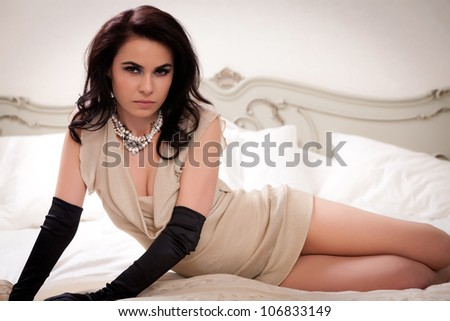 Young gorgeous brunette in sexy dress laying in a vintage style bed. - stock photo