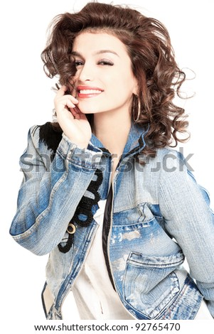 young gorgeous brunette model in jeans jacket, studio shot - stock photo