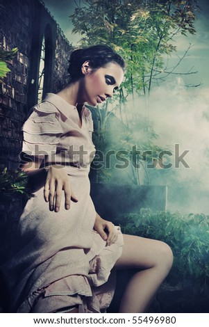 Young gorgeous brunette posing over mysterious smoky background - stock photo