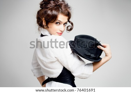 young gorgeous brunette posing with hat, studio shot - stock photo