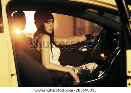 Young gorgeous fashion woman sitting in a car - stock photo