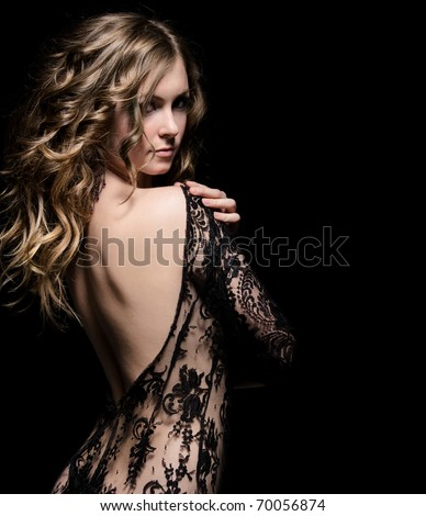 young gorgeous lady posing in lace dress, over black. space for copy - stock photo