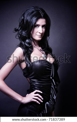 Young gorgeous woman posing in black dress, over black. space for copy