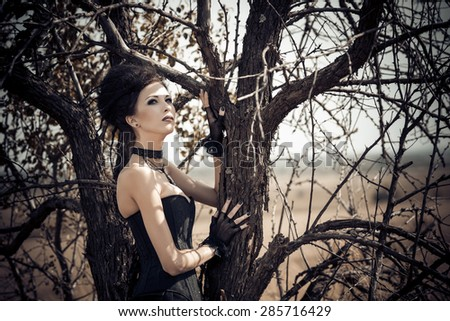 Young goth woman walking on field against a tree - stock photo