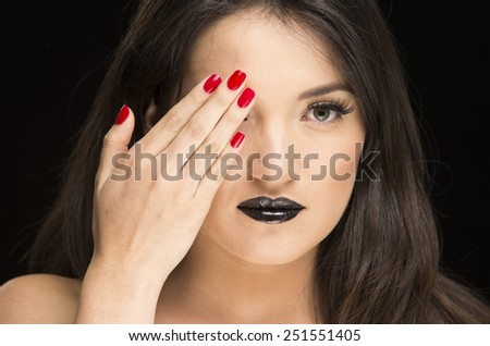 young gothic beautiful woman with black makeup and red nails covering one eye - stock photo