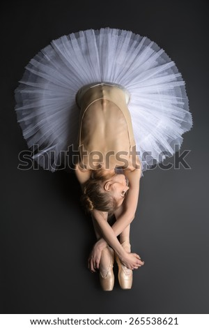 Young, graceful ballerina sitting on the floor on a black background in a studio in the slope face touching knees. Close-up. - stock photo