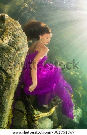 Young graceful woman in a long dress posing near the stairs in the lake - stock photo