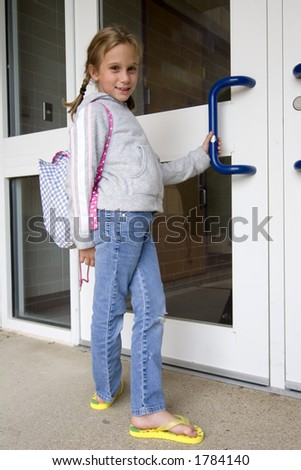 Young grade school age girl heading off to school - stock photo