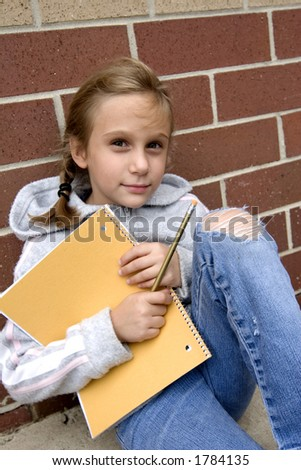 Young grade school age girl sitting outside school with notebook and pencil - stock photo