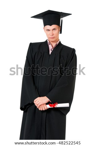 Young graduation man holding diploma. Male student dressed in black graduation gown. Teen boy looking at camera isolated on white background.