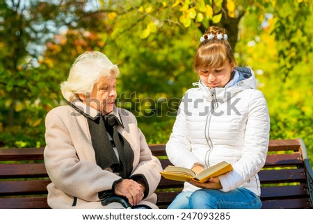 young granddaughter reads his elderly grandmother book - stock photo