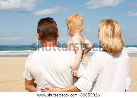 Young grandparents with a grandchild in her arms, on the sea - stock photo