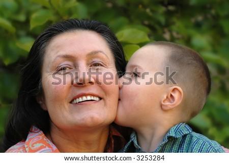 Young grandson giving his grandma a big smooch on the cheek - stock photo