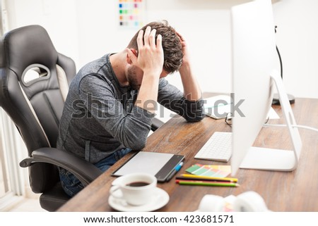 Young graphic designer feeling stressed and overwhelmed at work while putting his hands on his head