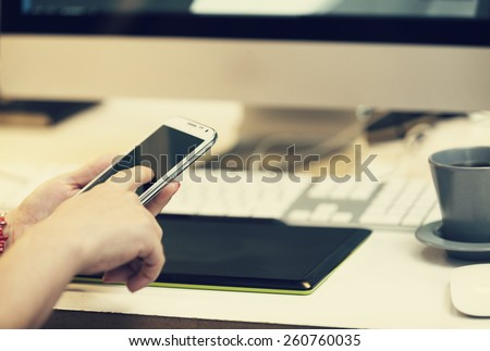 young graphic designer in the office checking her smart phone - stock photo