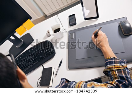 Young graphic designer working in office - stock photo