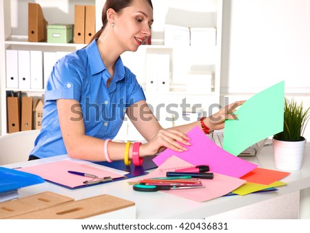 Young graphic designer working on laptop using tablet at home