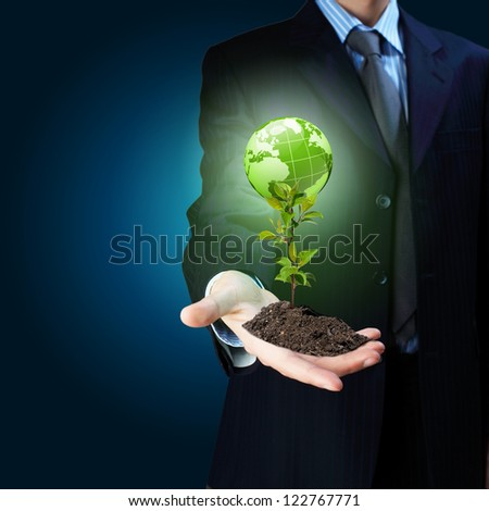 Young green plant in the hand of a businessman - stock photo