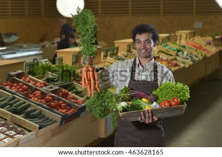 Young Grocery clerk working in produce aisle of grocery store
