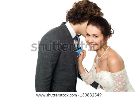 Young groom whispering into the ears of a gorgeous bride holding cash card. - stock photo