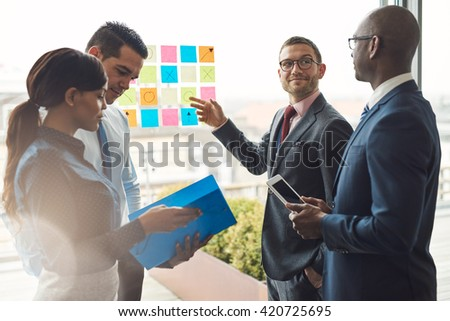 Young group of diverse business people in conference meeting using colorful sticky notes to organize ideas on large glass window - stock photo