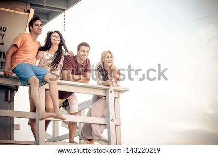 Young Group of Friends at the Beach on the Lifeguard stand in Southern California