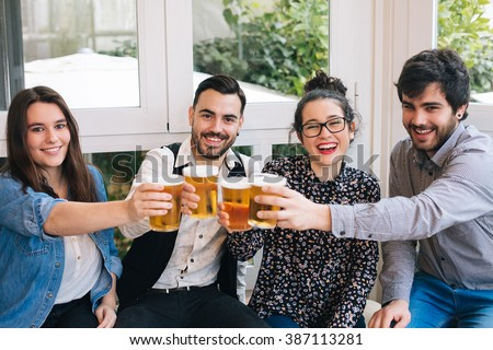 Young group of friends having fun in a bar toasting with beer - stock photo