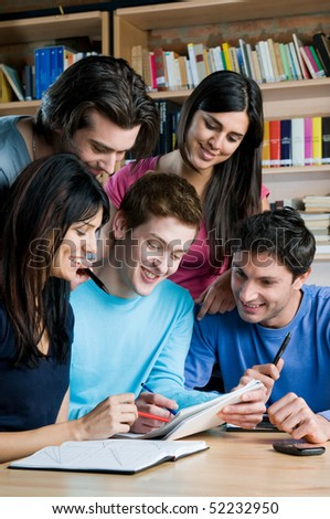 Young group of happy students studying and working together in a college library - stock photo
