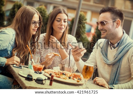 Young group of laughing people eating pizza and having fun.They are enjoying eating and drinking together. - stock photo