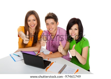 Young group of people show thumb up finger gesture point at you, top angle view of three students looking up at camera, excited smiling friends sitting at desk with laptop, isolated white background - stock photo