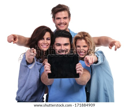 young group of people showing you the blank screen of a tablet pad computer and point fingers to the camera