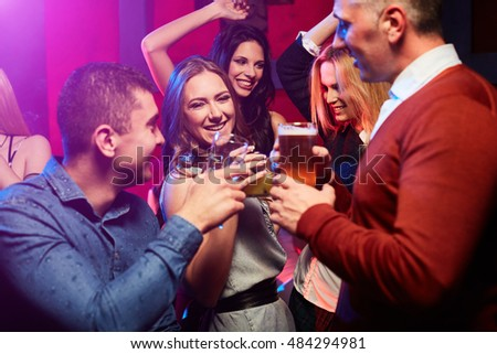 Young group of smiling people drinking beer and cocktails at the nightclub