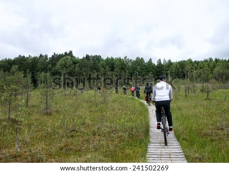 Young group riding bicycles by dirty road in countryside,group cyclists on a way between trees,young cyclists touring in Lithuania,bicycle in Lithuania, cycling bicycle,summer activities in Lithuania  - stock photo