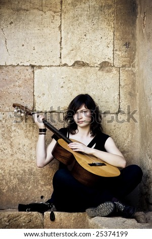 Young guitar performer against brickwall - stock photo