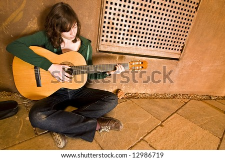Young guitar performer in urban background. - stock photo