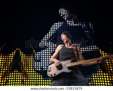 young guitar player at concert and led screen background - stock photo