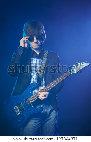 Young guitarist on stage standing in smoke lowering his sunglasses - stock photo