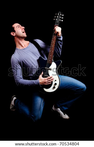 Young guitarist over a black background - stock photo