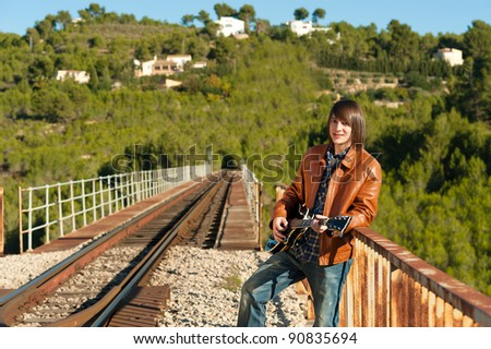 Young guitarist playing on a rusty railway bridge
