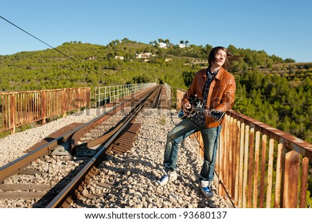 Young guitarist playing on a rusty railway bridge - stock photo
