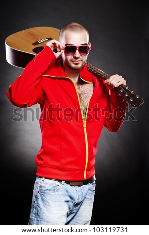 young guitarist stand and holds a guitar in his hands. on a black background - stock photo