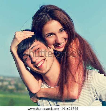 Young guy and girl having fun in the summer outdoors - stock photo