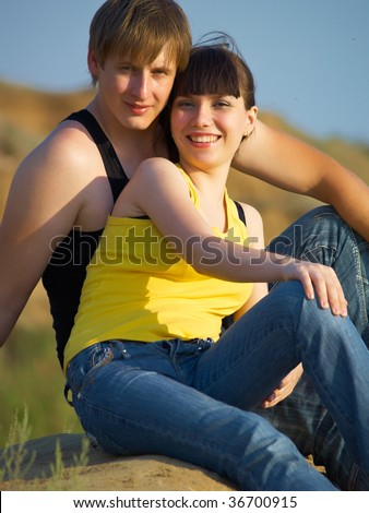 Young guy and the girl sit on the nature