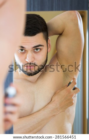 Young guy applying deodorant spray - stock photo