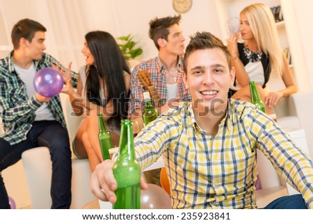 Young guy at a home party, with a smile on his face looking at the camera, holding a bottle of beer with which toasts the viewer. In the background you can see his friends sitting on the couch. - stock photo