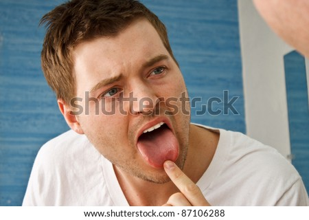 Young guy checking tongue in mirror