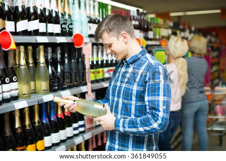 Young guy choosing bottle of wine at alcohol section in supermarket  - stock photo