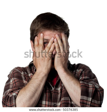 Young guy covers his face, scared of something - stock photo