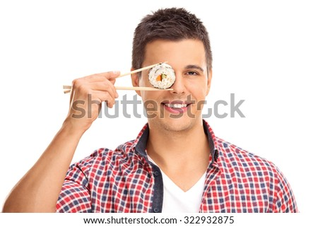Young guy holding a piece of sushi with Chinese sticks in front of his right eye and looking at the camera isolated on white background - stock photo