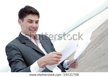 young guy in a business suit with joy looking documents - stock photo